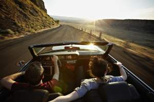 young-couple-driving-convertible-at-sunset